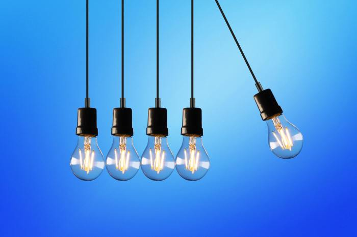 Digital transformation - Five suspended lightbulbs in a row with the fifth lightbulb set away from the rest against a blue backdrop.